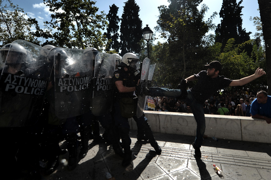 A demonstrator clashes with riot police during a 24-hour strike in Athens on October 18, 2012. Greek riot police fired tear gas to disperse protesters at an anti-austerity rally in Athens held during a national general strike as EU leaders were to tackle the eurozone crisis at a summit. The protesters had broken through a police line outside luxury hotels on central Syntagma Square and scattered groups of youths later attacked police with stones and firebombs, an AFP reporter said. AFP PHOTO / ARIS MESSINIS