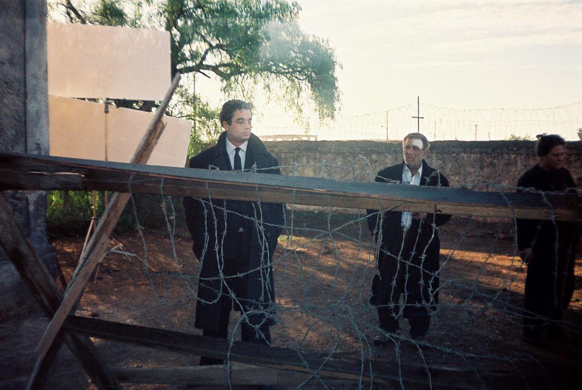 Ο Σωτήρης Κακίσης (αριστερά) διευθυντής φυλακών στον «Ηνίοχο» (1994), υπό το βλέμμα του Αλέξη Δαμιανού. Δεξιά η Άρτεμις Δαμιανού.