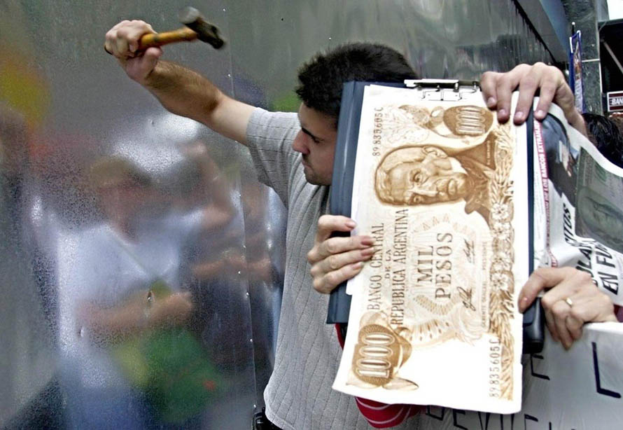 Argentines try to break down a metal wall at a bank in Buenos Aires in 2002 to protest the government-imposed blockade that had prevented access to their savings since the beginning of December 2001.