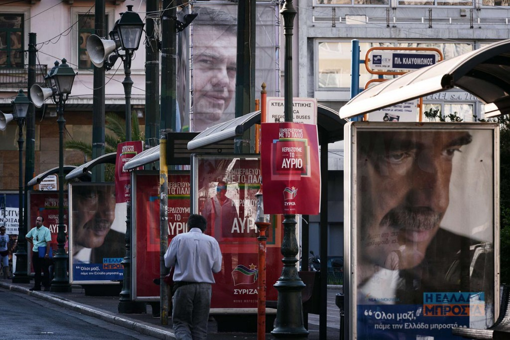 A man walks past pre-election posters featuring conservative New Democaracy leader Vangelis Meimarakis (R) and leftist Syriza leader Alexis Tsipras in central Athens on September 16, 2015. With Greece's snap elections on September 20, the top two parties are neck and neck in the polls. Analysts say a full return to power for the leftist Syriza party, while still possible, is unlikely. AFP PHOTO/ LOUISA GOULIAMAKI