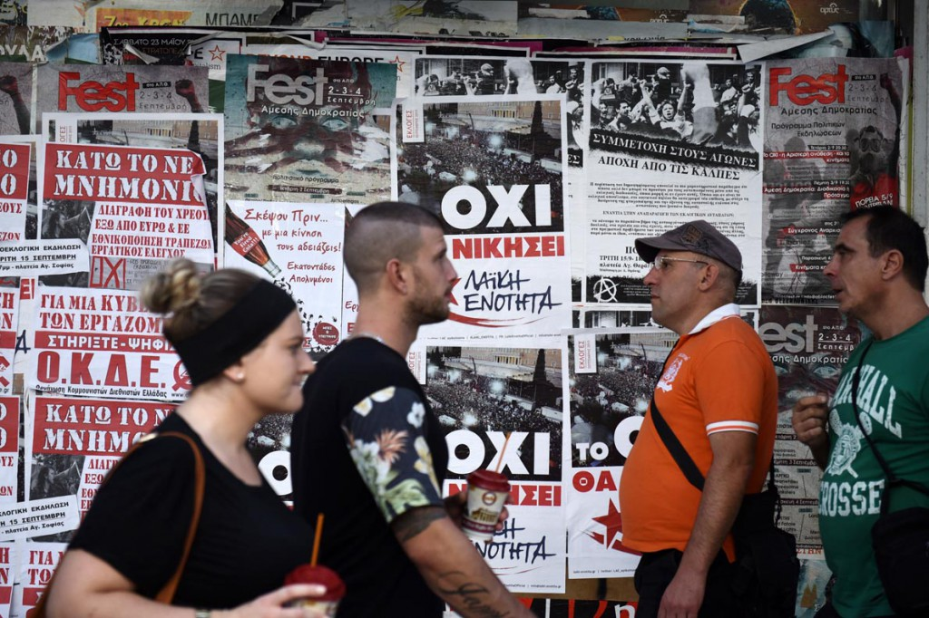 Pedestrians pass posters of left-wing parties in the northern Greek city of Thessaloniki, Tuesday, Sept. 15, 2015. Alexis Tsipras the leader of left-wing party leader Syriza and former Prime Minister Alexis Tsipras called a snap election for Sunday, Sept. 20 after reaching an agreement with eurozone countries for a third bailout, and has clung to a slim lead in opinion polls despite a sharp drop in his approval ratings. (AP Photo/Giannis Papanikos)
