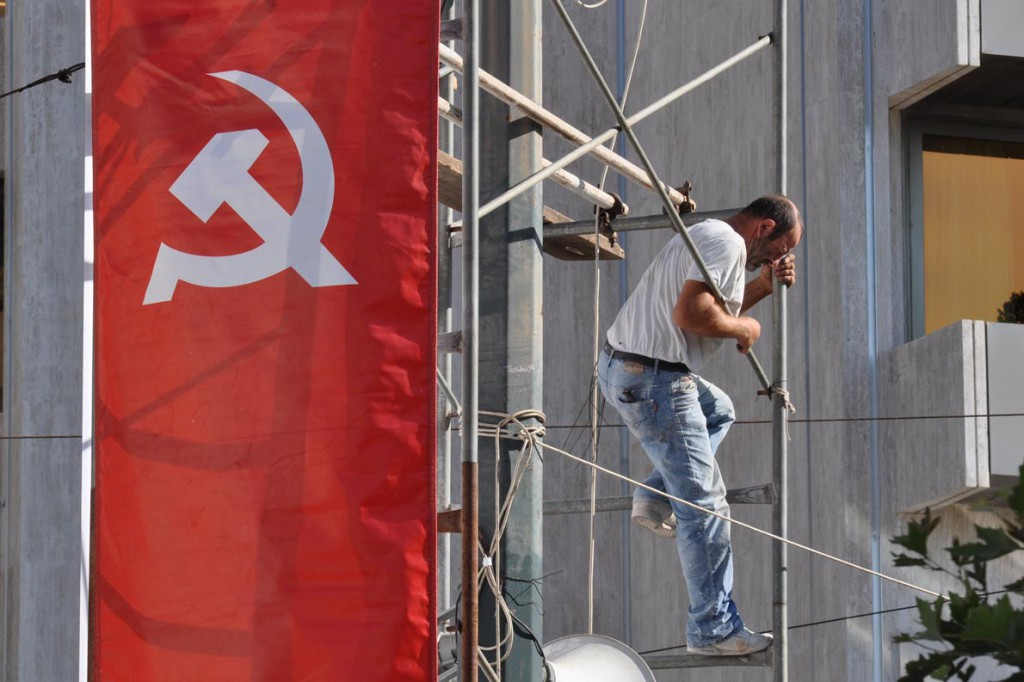 A worker climbs on scaffolding as he prepares the venue for the Greek Communist Party party election rally in Athens, Greece, September 16, 2015. The outcome of Sunday's Greek national election looks more uncertain than ever after the country's two dominant politicians ruled out working with each other and apparently failed to sway undecided voters in a final televised debate. REUTERS/Michalis Karagiannis
