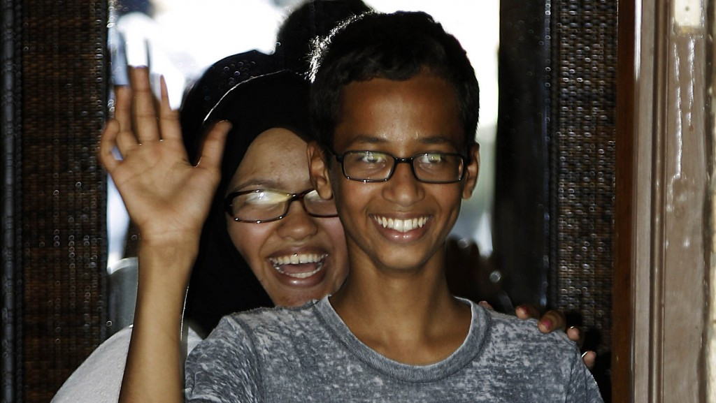 Ahmed Mohamed, 14, right, waves to the media from the front door of his house as his sister, Eyman Mohamed, looks on before a news conference, Wednesday, Sept. 16, 2015, in Irving, Texas. Ahmed was arrested after a teacher thought a homemade clock he built was a bomb. (AP Photo/Brandon Wade)