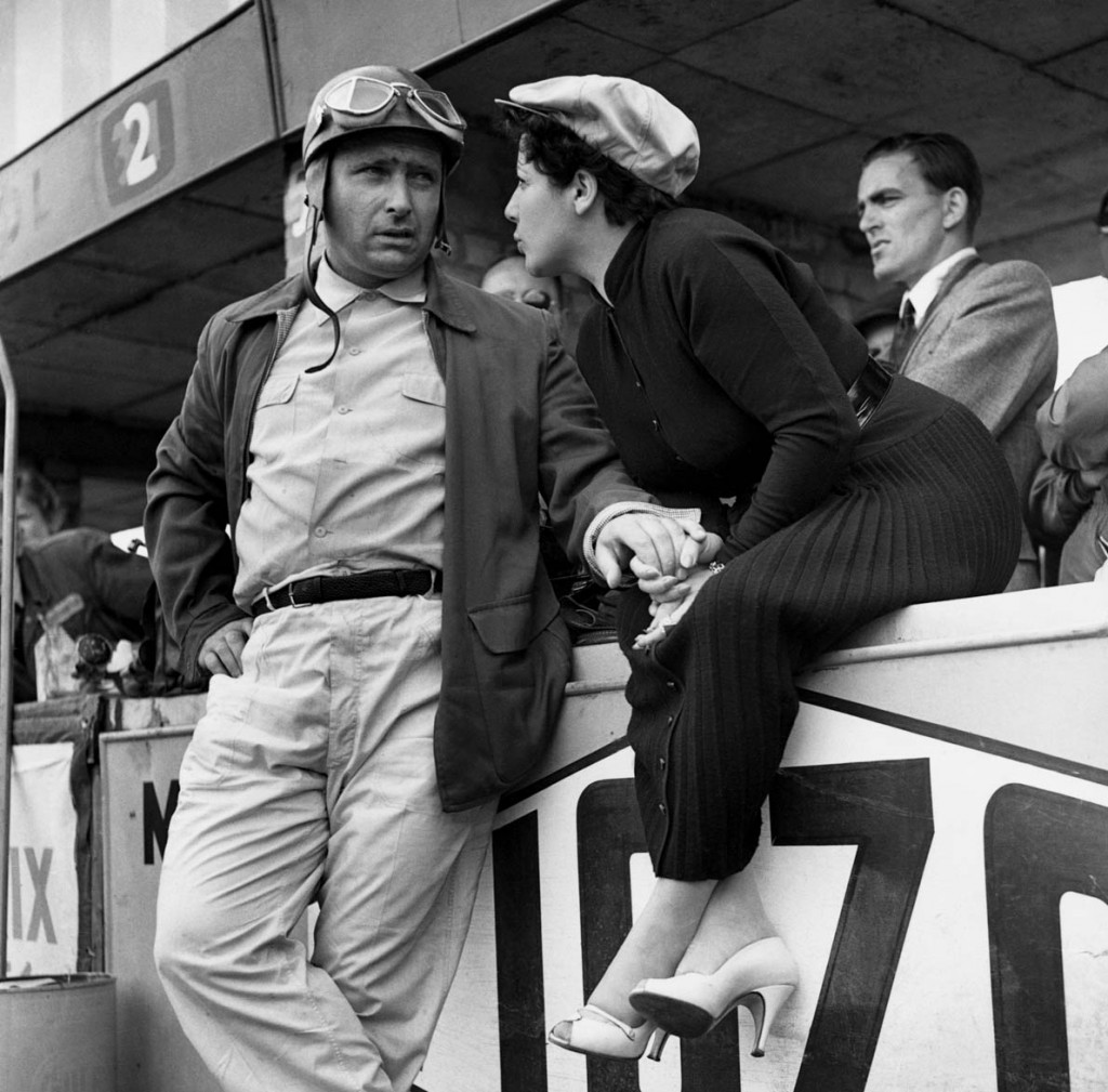 1954, Silverstone, Northamptonshire, England, UK --- Argentine Juan Manuel Fangio, the five-time world motor racing champion, talks to his wife at the Silverstone racing circuit in Northamptonshire, where is participating in the Cuban Grand Prix. England, 1954. --- Image by © Hulton-Deutsch Collection/CORBIS