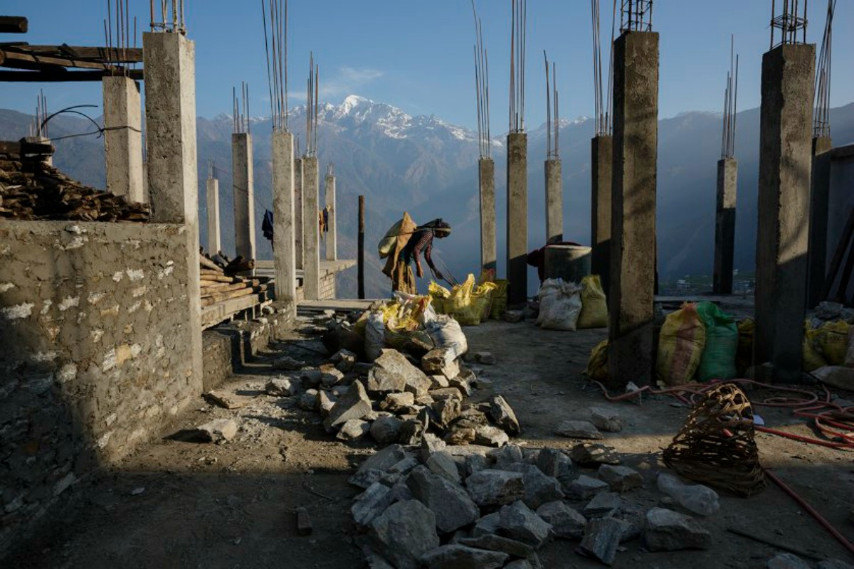 The village of Barpak, in Gorkha district, close to the epicenter of the earthquake, which destroyed almost the entire village. Villagers rebuilding houses and pathways and building a new religious stupa. Much of the work is accomplished communally. Buddha Himal mountain in background. by James Nachtwey