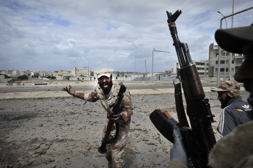 National Transitional Council fighters fire against troops loyal to Moamer Kadhafi in Sirte on October 10, 2011. AFP PHOTO / ARIS MESSINIS