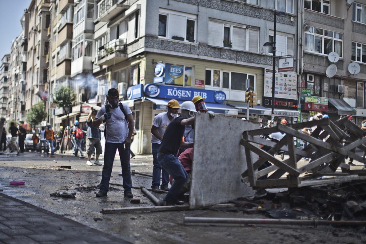 Διαδηλωτές έχουν καλυφθεί πίσω από ένα αυτοσχέδιο οδόφραγμα κατά τη διάρκεια συγκρούσεων με την αστυνομία.