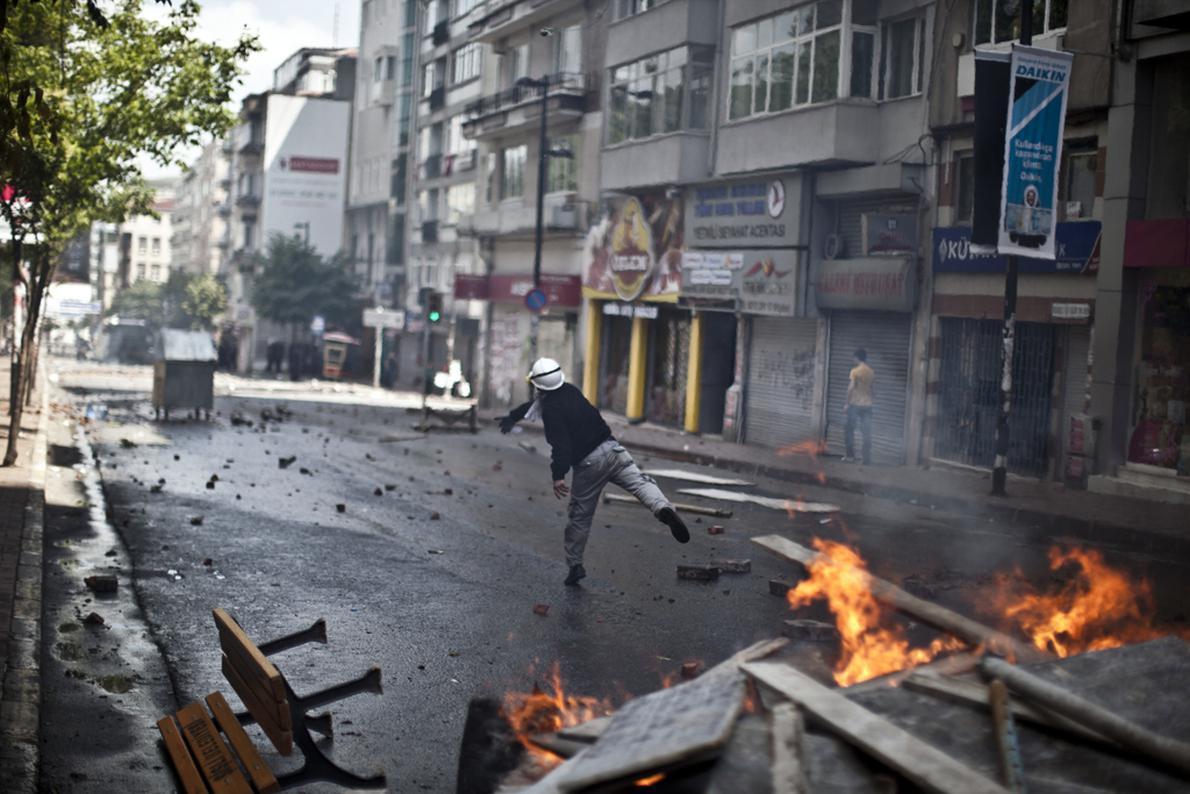 Διαδηλωτής εκτοξεύει μία πέτρα προς τις γραμμές της αστυνομίας στην περιοχή Kurtulus.