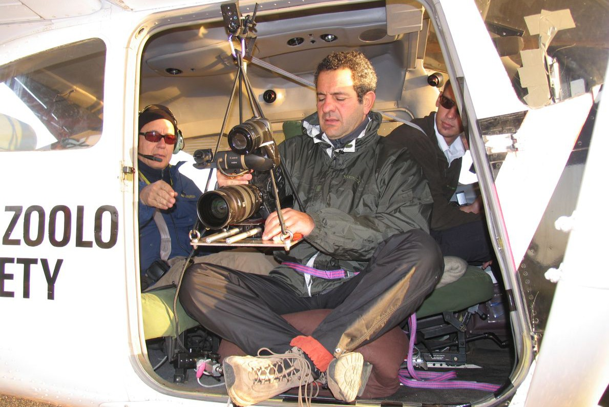 Με το αεροπλάνο ζέβρα του Ζωολογικού Κήπου της Φρανκφούρτης: ο Ανδρέας Αποστολίδης (αριστερά), ο διευθυντής φωτογραφίας Στέλιος Αποστολόπουλος και πιλότος ο νεαρός Μπόρνερ, γιoς του σημερινού υπεύθυνου της FZS στο Σερενγκέτι. Για καλύτερο γύρισμα αφαίρεσαν την αριστερή πόρτα του αεροπλάνου.