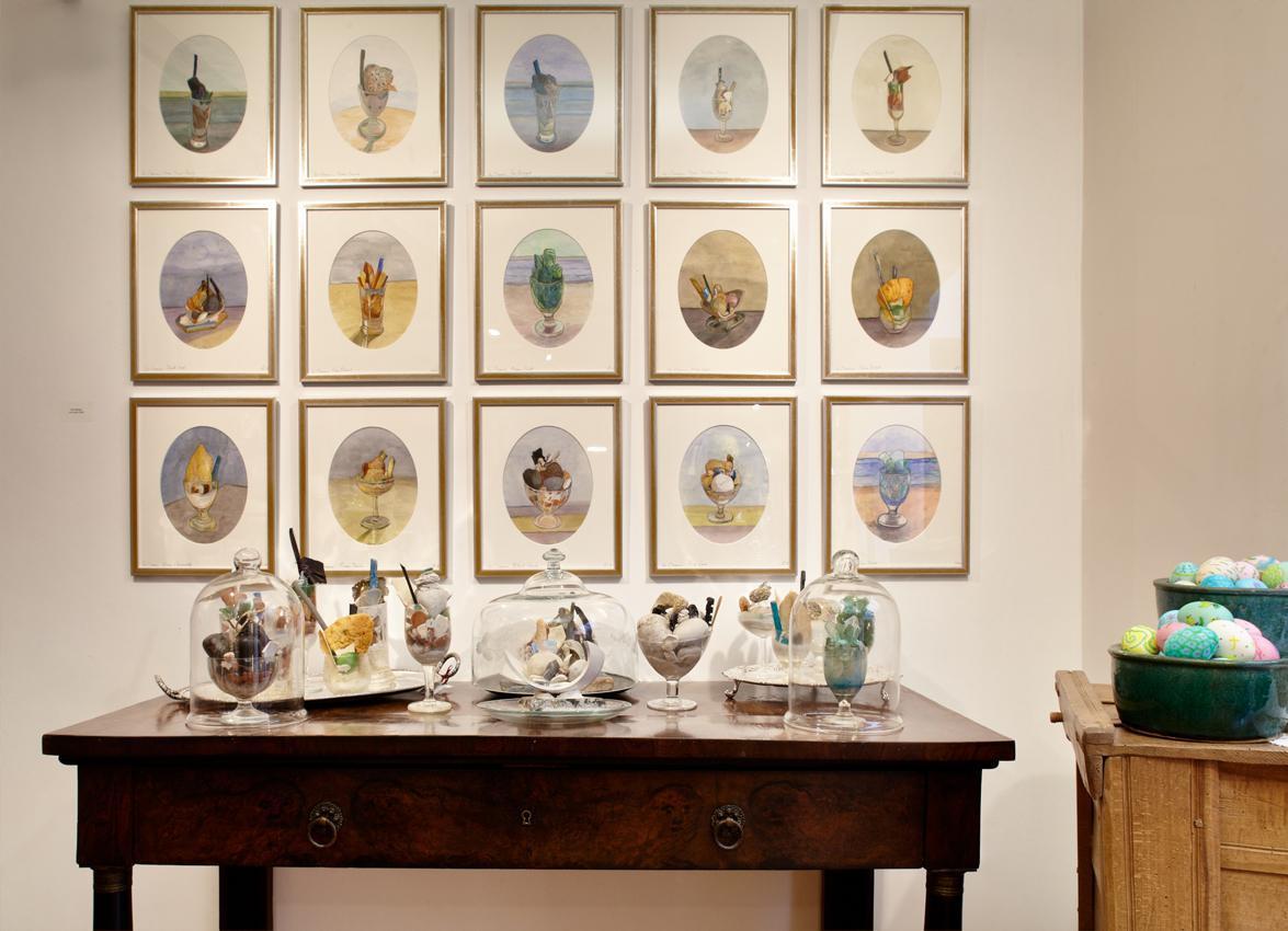 Ακουαρέλες και γλυπτά της Λίζης Καλλιγά ακουμπισμένα σε μια κονσόλα.