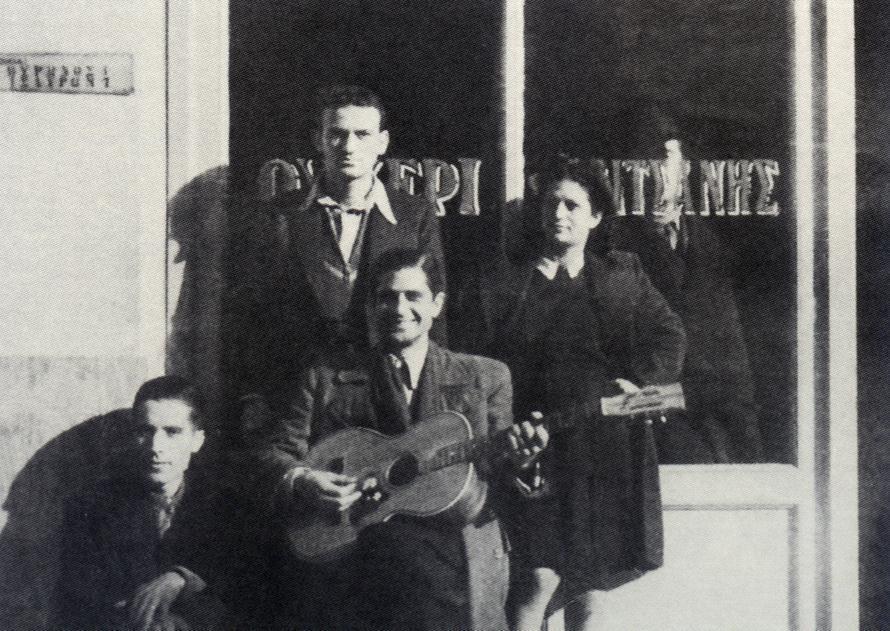 Έξω από το «Ουζερί Τσιτσάνης». Όρθιος ο Ανδρέας Σαμαράς (κουνιάδος του Τσιτσάνη), κάτω δεξιά ο κιθαρίστας και τραγουδιστής Γιάννης Κυριαζής.