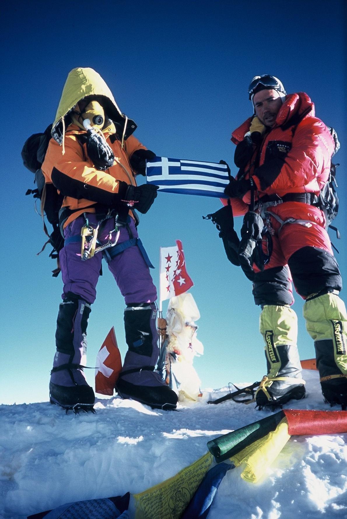 Ξημερώματα της 16ης Μαΐου 2004 στη κορυφή των κορυφών ο Γιώργος Βουτυρόπουλος (δεξιά με τα κόκκινα) σε ένα ενσταντανέ ζωής με τον Νεπαλέζο Pema Sherpa. «Έμεινα στην κορυφή 20 λεπτά. Ήταν πανέμορφα στο υπόφως του πρωινού», θυμάται. «Ύψωσα την ελληνική σημαία, φωτογραφήθηκα με αυτήν, άφησα και μια φωτογραφία του Χρήστου Μπαρούχα, που θα 'θελα να ήταν μαζί μας...»