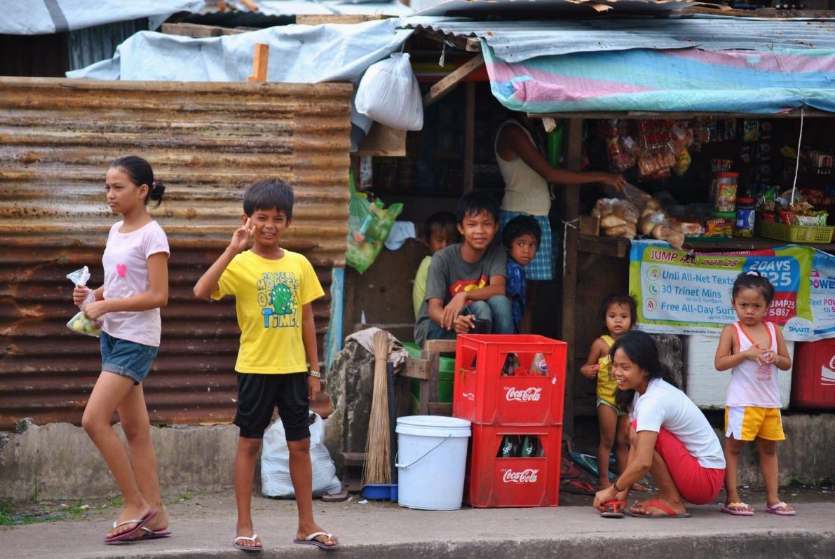Παιδιά χαιρετάνε το φακό έξω από τα πρόχειρα μικρομάγαζα που έχουν ανοίξει παντού, σε μια προσπάθεια των κατοίκω να εξασφαλίσουν ένα κάποιο εισόδημα.