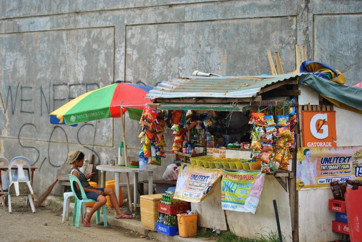 Νεαρό κορίτσι πουλάει ψιλικά είδη, με φόντο στον τοίχο την έκκληση (στα αγγλικά) «Χρειαζόμαστε βοήθεια».
