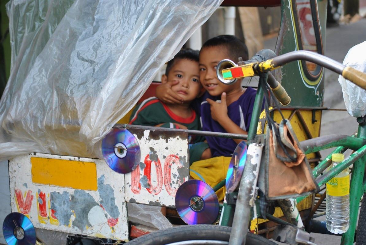 Δυο μικρά αγόρια χαιρετάνε μέσα από ένα «pedicamb». Τα «pedicamb», αποτελούμενα από ένα μοτοποδήλατο και μια θέση για τον επιβάτη, λειτουργούν ως ταξί. Μετά τον τυφώνα ο αριθμός τους έχει διπλασιαστεί, καθώς συνιστούν μια εναλλακτική λύση εργασίας για τους άνεργους άντρες.