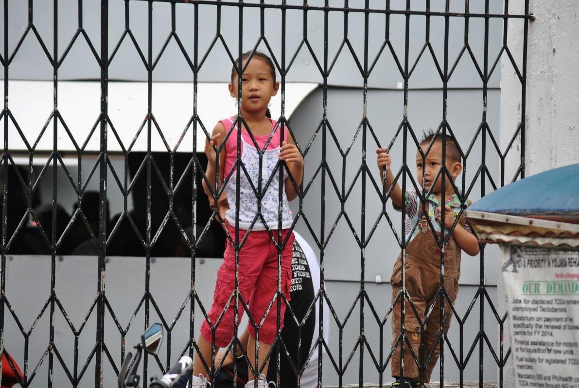 Δύο μικρά αδέρφια σκαρφαλώνουν στα κάγκελα της τοπικής εκκλησίας. Η Ρωμαιοκαθολική εκκλησία παραμένει ο πιο ισχυρός θεσμός στις Φιλιππίνες.