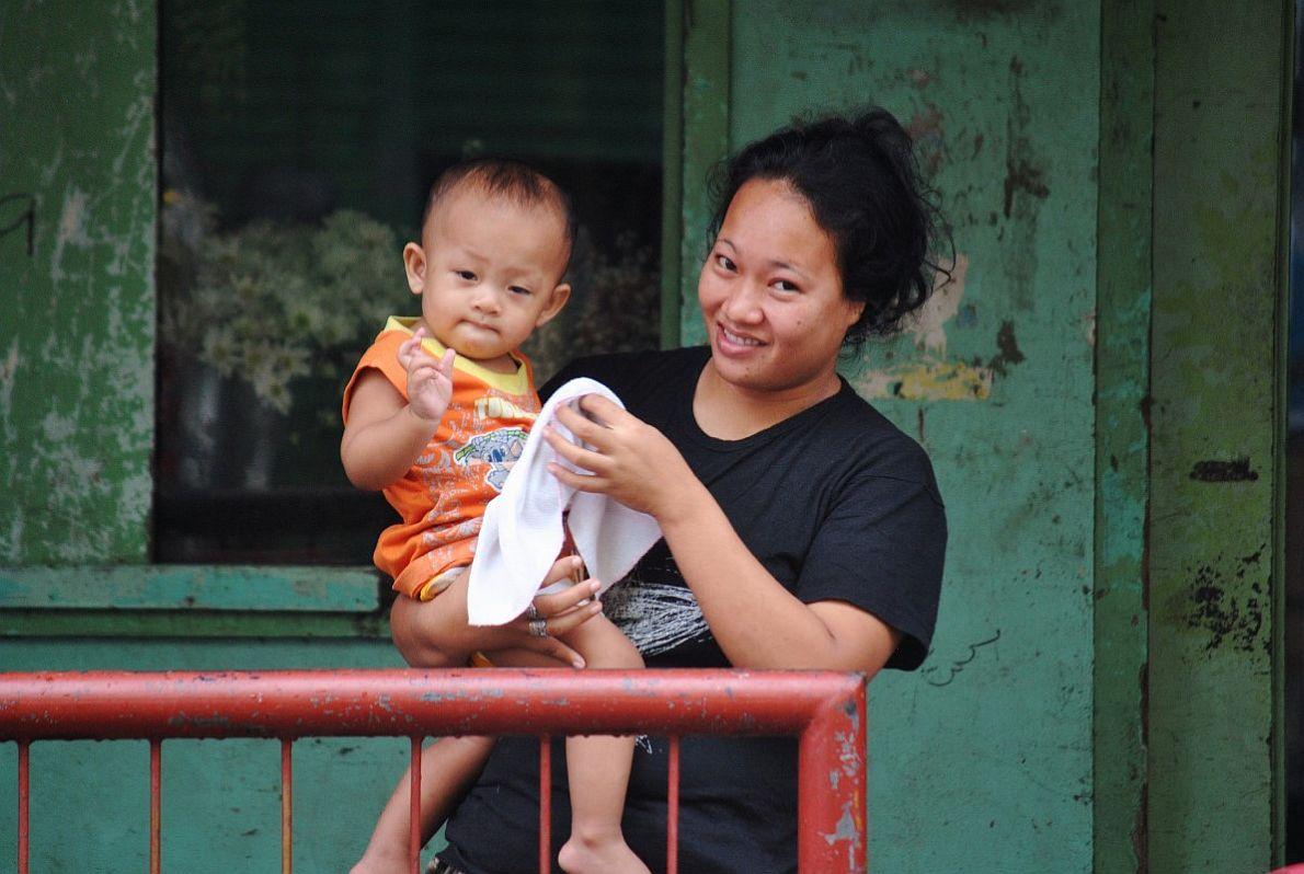 Νεαρή μητέρα με το μωρό της στην είσοδο του σπιτιού τους.
