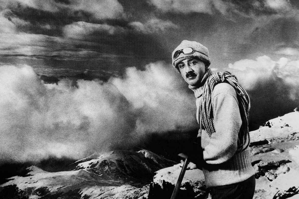 ο Νικόλαος Τομπάζης με φόντο τις λευκές κορυφές των βουνών Σκίμ. Η αδύνατη φιγούρα με το μελαγχολικό βλέμμα θαρρείς ισορροπεί στην άκρη του χρόνου, εκεί όπου σμίγει ο ουρανός με τη γη.